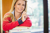 Smiling mature student with stack of books holding glasses