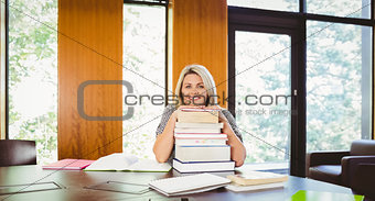 Smiling blonde mature student with stack of books