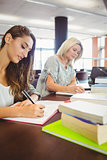 Matures females students writing notes at desk
