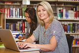 Smiling mature female students using her laptop