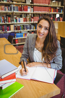 Smiling brunette student doing her assignment
