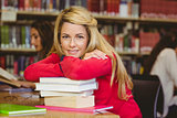 Smiling mature student leaning on a stack of books