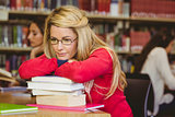 Thoughtful mature student leaning on a stack of books
