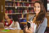 Pretty student holding books with classmates behind her