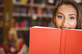 Pretty brunette student holding book in front of her face