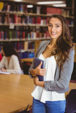Pretty student holding tablet with classmates behind her