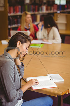 Focused student sitting at desk reading text book
