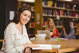 Smiling student sitting at desk reading text book