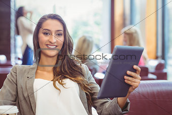 Student using digital tablet and holding disposable cup