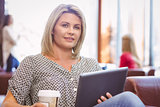 Smiling woman using digital tablet and holding disposable cup