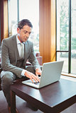 Focused handsome businessman working at laptop