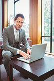 Smiling handsome businessman working at laptop