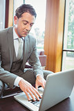 Focused handsome businessman using his laptop