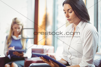 Thoughtful businesswomen using digital tablet