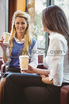 Business colleagues holding coffee cup and digital tablet