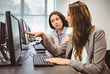 Serious businesswomen looking at computer screen together