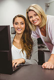 Smiling teacher and student behind desk at computer