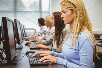 Four focused women working in computer room