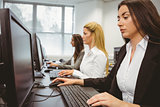 Three focused women working in computer room