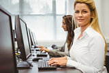 Happy woman in computer room smiling at camera