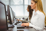 Two focused women working in computer room