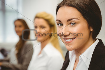 Happy women in computer room smiling at camera