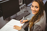 Smiling student sitting at desk writing on notepad
