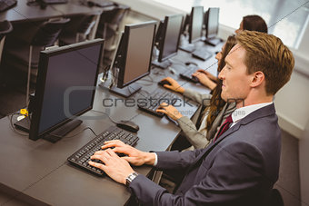 Three focused people working in computer room