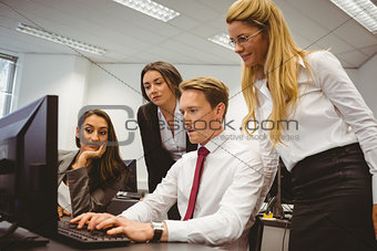 Casual boss showing something to his business team