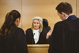Judge wearing a dress and a wig speaking with lawyers