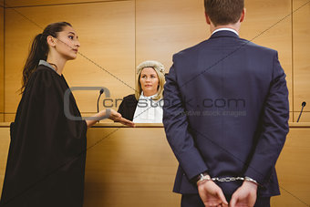 Lawyer talking with the criminal in handcuffs