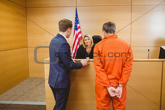 Lawyer and judge speaking next to the criminal in handcuffs