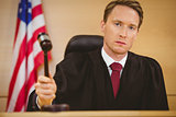 Serious judge about to bang gavel on sounding block