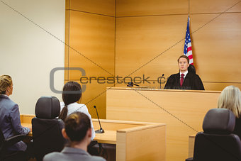 Unsmiling judge with american flag behind him