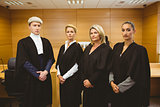 Four serious judges standing while wearing robes