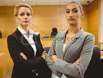 Two serious lawyers standing with arms crossed