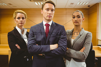 Three serious lawyers standing with arms crossed