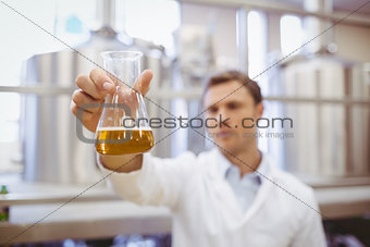 Thoughtful scientist holding a beaker