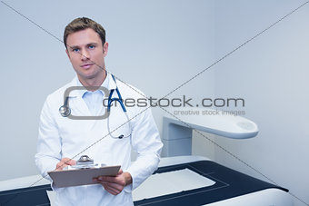 Portrait of smiling doctor writing on clipboard
