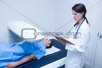 Focused doctor writing on clipboard