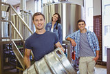 Young man holding keg with these colleagues behind him