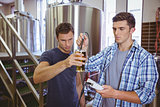 Two casual men testing beer