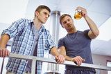 Men holding beaker with beer