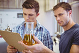 Two men looking at the beaker with beer