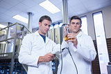 Two men in lab coat testing beer in the beaker