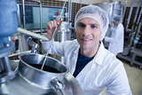 Smiling scientist using brewer in the container