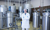 Scientist with arms crossed standing in front of container