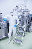 Scientist in protective suit leaning against machine