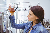 Stylish brunette in denim jacket looking at beaker of beer