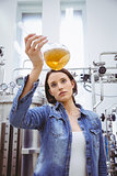 Stylish girl in denim jacket holding beaker of beer